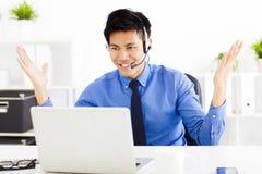 佩带耳机和工作在办公室的商人 免版税库存照片