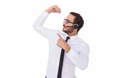 佩带耳机的商人,当显示某事时 免版税库存图片