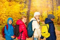 佩带背包的后面观点的愉快的孩子 免版税库存照片