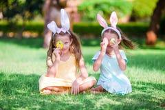 佩带自复活节前夕的两个小女孩兔宝宝耳朵户外 免版税库存照片