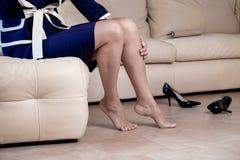 佩带蓝色和白色的播种的画象底视图妇女` s腿穿戴黑高跟鞋鞋子坐白色扶手椅子接触 免版税库存图片
