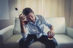 佩带蓝色宽松领带的醺酒的商人喝与在长沙发的威士忌酒瓶 免版税库存图片