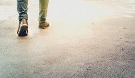 佩带蓝色牛仔裤和bown运动鞋againt太阳的腿特写镜头  免版税库存照片