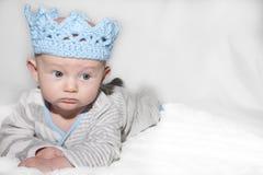 佩带蓝色编织冠的严厉的婴孩 免版税库存照片