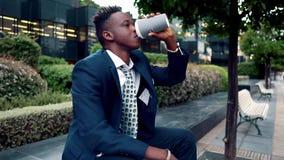 佩带蓝色衣服饮料咖啡的非裔美国人的商人在办公室附近 股票录像