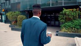 佩带蓝色衣服饮料咖啡的非裔美国人的商人在办公室附近 股票视频