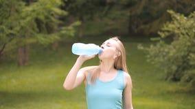 佩带蓝色T恤杉饮用水的年轻美丽的深色头发的妇女画象在夏天 股票视频