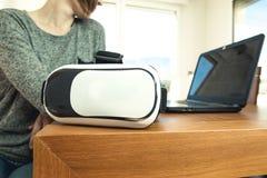 佩带虚拟现实玻璃和一台膝上型计算机的年轻女人在办公室 VR玻璃,娱乐,技术 免版税库存图片