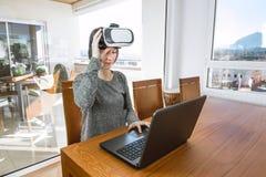 佩带虚拟现实玻璃和一台膝上型计算机的年轻女人在办公室 VR玻璃,娱乐,技术 图库摄影