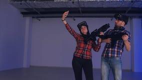 佩带虚拟现实玻璃和枪的年轻夫妇采取在电话的selfies 免版税库存照片