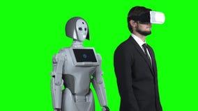 佩带虚拟现实玻璃和a的人投入他的手对边,并且机器人在他以后重复 绿色屏幕 慢 影视素材