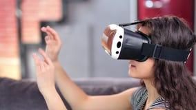 佩带虚拟现实盔甲模拟器的特写镜头年轻吃惊的妇女享用3d网际空间 股票录像