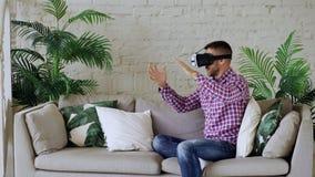佩带虚拟现实耳机的年轻快乐的人有360个VR录影经验,当坐长沙发在客厅时 免版税库存图片