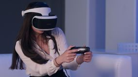 佩带虚拟现实设备和打与gamepad的妇女电子游戏 免版税库存图片