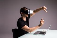 佩带虚拟现实风镜和打电子游戏的年轻人指向了与手指 赌博概念 库存照片