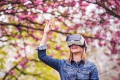 佩带虚拟现实风镜外面在春天自然的妇女 库存图片