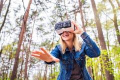 佩带虚拟现实风镜外面在春天自然的妇女 免版税库存照片