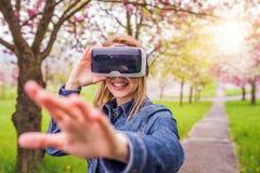佩带虚拟现实风镜外面在春天自然的妇女 库存照片