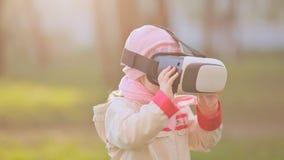 佩带虚拟现实风镜的小女孩观看电影或打电子游戏 看在VR的快乐的微笑的孩子 影视素材