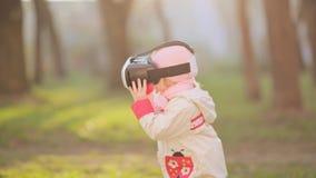 佩带虚拟现实风镜的小女孩观看电影或打电子游戏 看在VR的快乐的微笑的孩子 股票录像