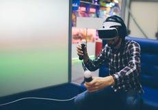 佩带虚拟现实风镜的有胡子的人在现代coworking的演播室 智能手机使用与VR耳机 水平 库存照片