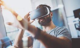 佩带虚拟现实风镜的有胡子的年轻人特写镜头在现代coworking的演播室 智能手机使用与VR 库存图片