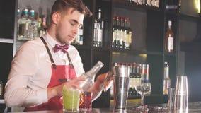 佩带蝶形领结、白色衬衫和红色围裙的男服务员做鸡尾酒在酒吧柜台在餐馆 影视素材