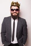 佩带衣服和冠的太阳镜的年轻英俊的人保留在他的夹克的手,当站立时 图库摄影