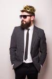 佩带衣服和冠的太阳镜的年轻英俊的人保留在他的夹克的手 免版税库存图片