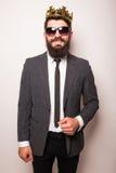 佩带衣服和冠的太阳镜的年轻英俊的人保留在他的夹克的手 免版税图库摄影