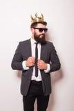 佩带衣服和冠的太阳镜的年轻英俊的人保留在他的夹克的手 免版税库存照片