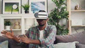 佩带被增添的现实玻璃和移动的手的非裔美国人的年轻人放大微笑和emjoying比赛 股票视频