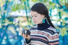 佩带被编织的雪花的妇女仿造喝热的yerba伙伴的毛线衣和绿松石耳环 图库摄影