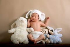 佩带褐色的新出生的男婴编织了兔子帽子和裤子, s 库存图片