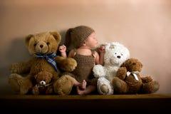 佩带褐色的新出生的男婴编织了熊帽子和裤子, sle 图库摄影