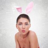 佩带逗人喜爱的兔宝宝的妇女送亲吻 库存图片