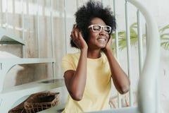 佩带逗人喜爱的白色镜片和享受音乐的非洲夫人 免版税图库摄影