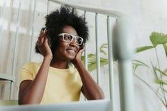 佩带逗人喜爱的白色镜片和听到音乐的非洲夫人 免版税库存照片