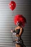 佩带钉胸罩的性感的小丑,当拿着一个红色气球时 免版税库存图片