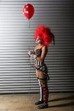佩带钉胸罩的性感的小丑,当拿着一个红色气球时 免版税图库摄影