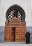 佩带阿拉伯djellaba的人在清真寺入口旁边 免版税库存图片