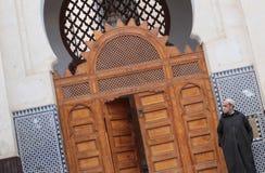 佩带阿拉伯djellaba的人在清真寺旁边 免版税图库摄影