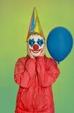 佩带面具和气球的小丑 免版税库存照片