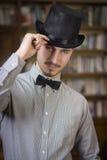 佩带高顶丝质礼帽和蝶形领结的典雅的年轻人 库存图片