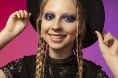 佩带黑哥特式d的一个美丽的微笑的白肤金发的十几岁的女孩 免版税图库摄影