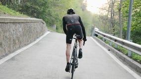 佩带黑成套装备骑马的坚强的骑自行车者艰难在马鞍外面 r 路自行车 影视素材