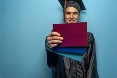佩带黑披风和灰泥板的毕业生男生 库存照片