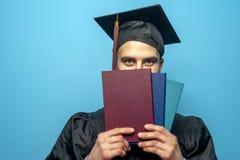 佩带黑披风和灰泥板的毕业生男生 库存图片