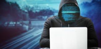 佩带黑敞篷的黑客的综合图象,当使用在桌上时的膝上型计算机 免版税库存图片