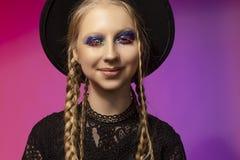 佩带黑色的一个美丽的微笑的闪光的白肤金发的十几岁的女孩 免版税库存图片